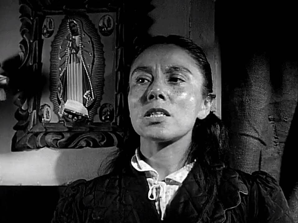 Rosaura Revueltas in the film with a picture of the Virgin of Guadalupe behind her.