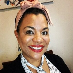 Dr. Jeanette Wade seated and smiling wearing a black and white polka dot shirt and scarf and a pink headband.