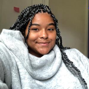 Kiwani Taylor smiling and wearing a gray sweater